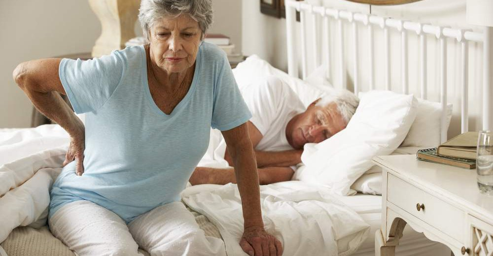 Senior woman waking up to back pain and sitting on side of bed agonizing in pain.