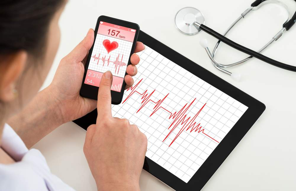 doctor using apps and technology to help monitor a patients health.