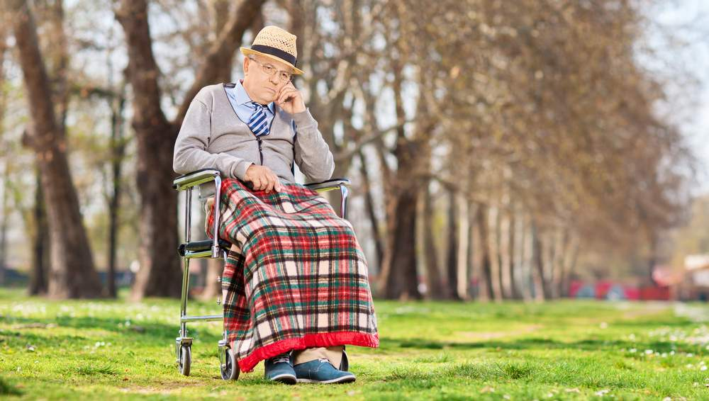 stereotype Grumpy old man sitting in a wheelchair outdoors