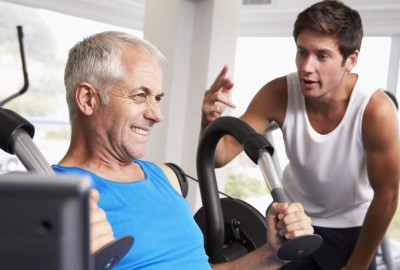 Aging man being encouraged by his trainer to exercise and live healthy