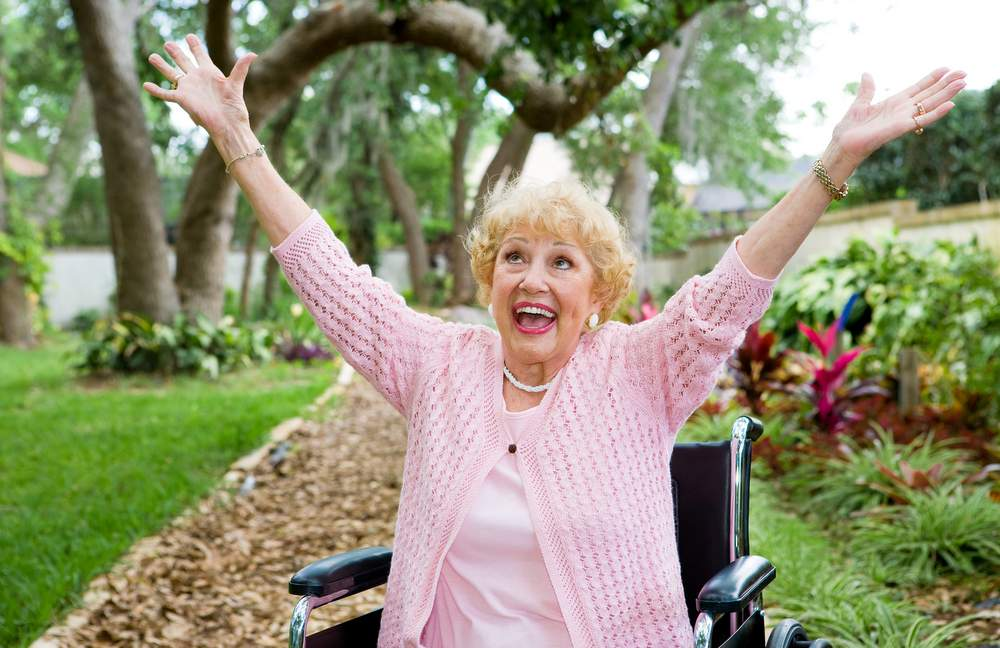 joyful elderly woman walking around at assisted living home showing pure happiness.