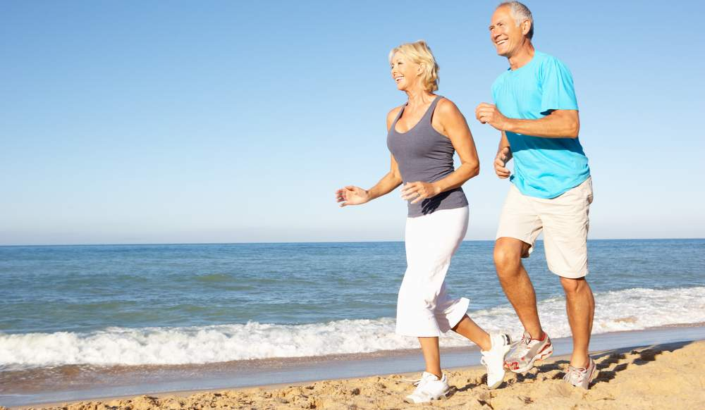 Senior Couple In Fitness Clothing Running Along Beach because exercising improves mental health