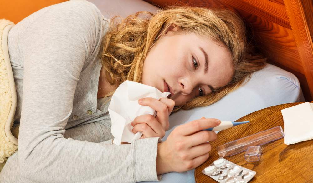 Woman sick with cold in bed with Thermometer And Pills.