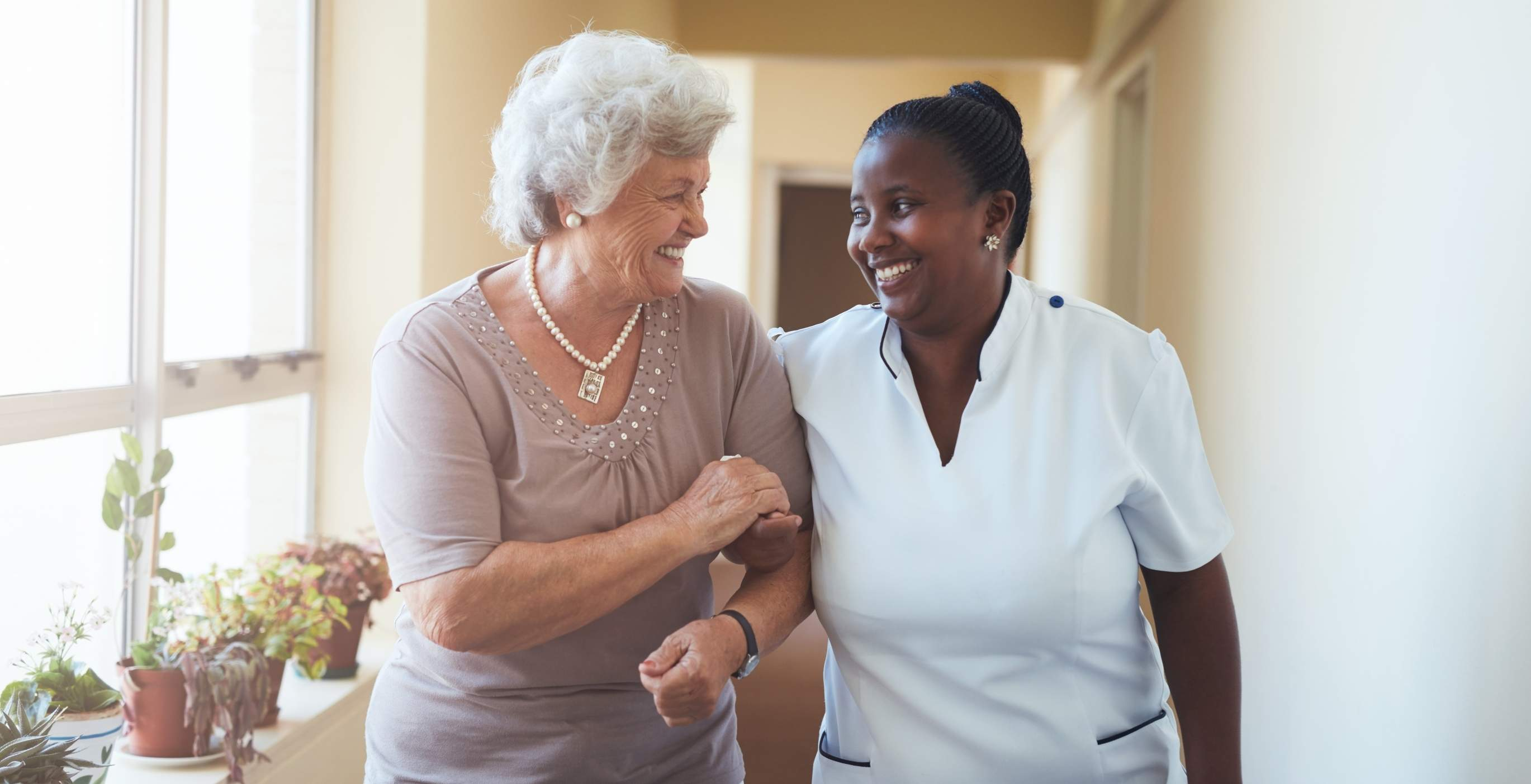 Smiling Home Caregiver And Senior Woman Walking Together to new beginnings
