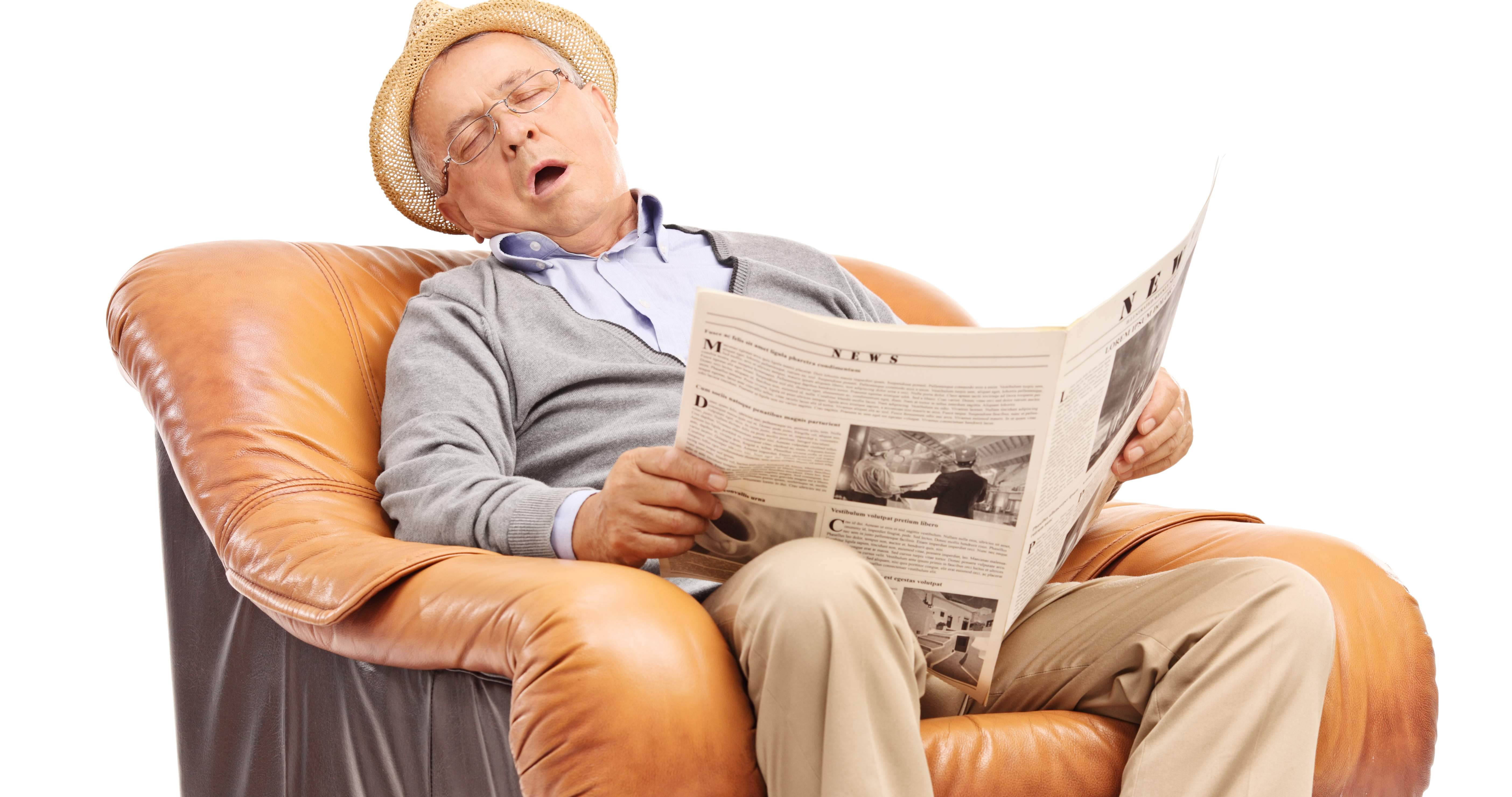 tired senior man sleeping and reading a newspaper