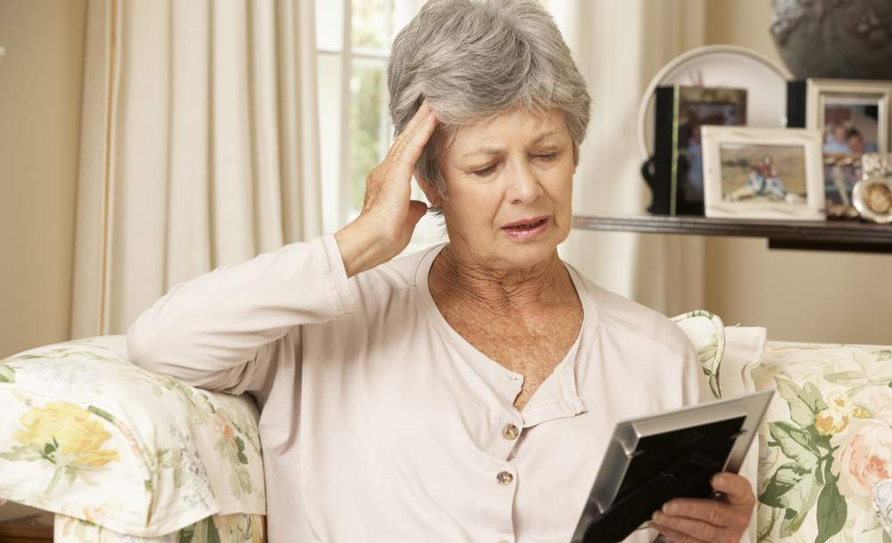 elderly woman with dementia struggling to remember. very forgetful due to senior natural senior forgetfulness