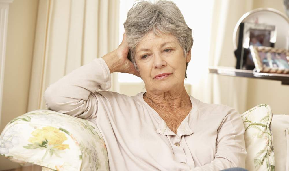 unhappy lonely retired senior sitting on sofa at home alone and isolated