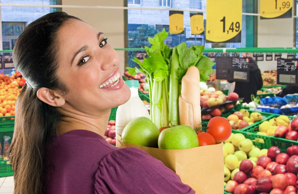Woman holding groceries filled with healthy vegetables and colorful foods