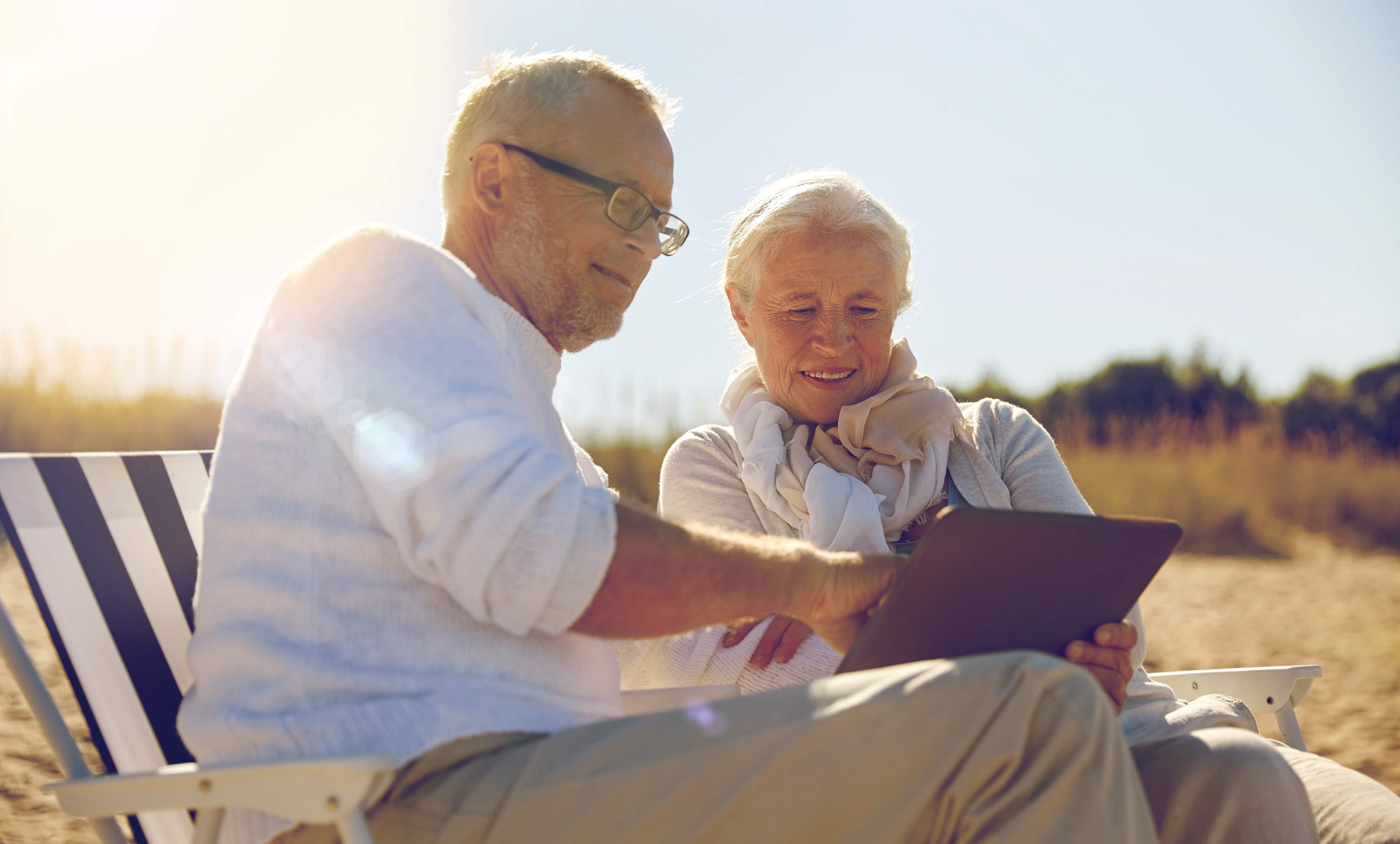 senior couple planning retirement on beach
